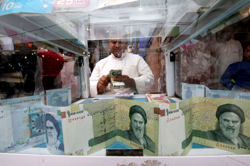 © Reuters. FILE PHOTO: A man counts Iranian rials at a currency exchange shop, before the start of the U.S. sanctions on Tehran, in Basra