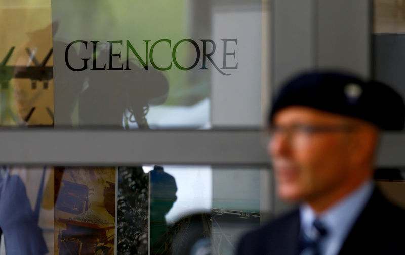 © Reuters. FILE PHOTO: An employee of a private security company stands in front of the logo of commodities trader Glencore in Cham