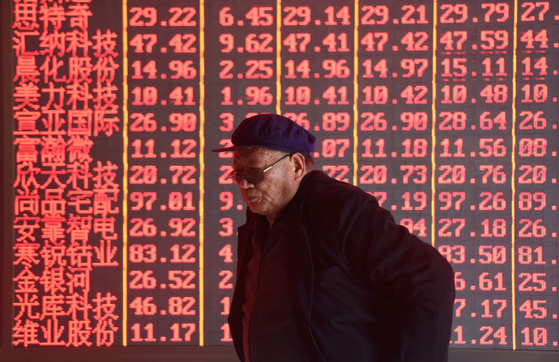 © Reuters. Man stands in front of an electronic board displaying stock information at a brokerage firm in Hangzhou