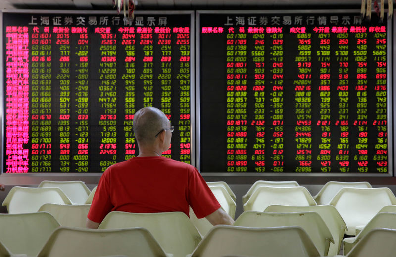 © Reuters. FILE PHOTO: An investor watches stock prices at a brokerage office in Beijing