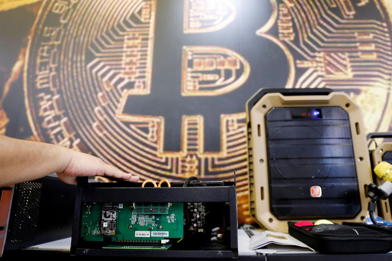 © Reuters. A cryptocurrency mining computer is seen in front of bitcoin logo during the annual Computex computer exhibition in Taipei