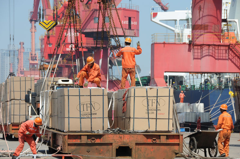 © Reuters. FILE PHOTO: Workers load goods for export onto a crane at a port in Lianyungang