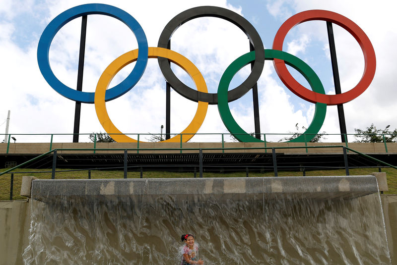 © Reuters. A child plays in water near Olympic rings placed at Madureira Park ahead of the Rio 2016 Olympic Games in Rio de Janeiro