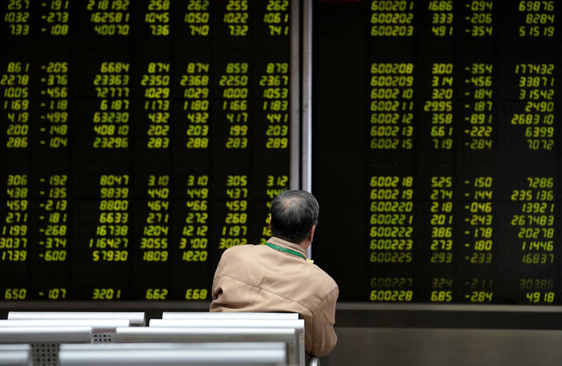 © Reuters. FILE PHOTO: An investor looks at a board showing stock information at a brokerage office in Beijing