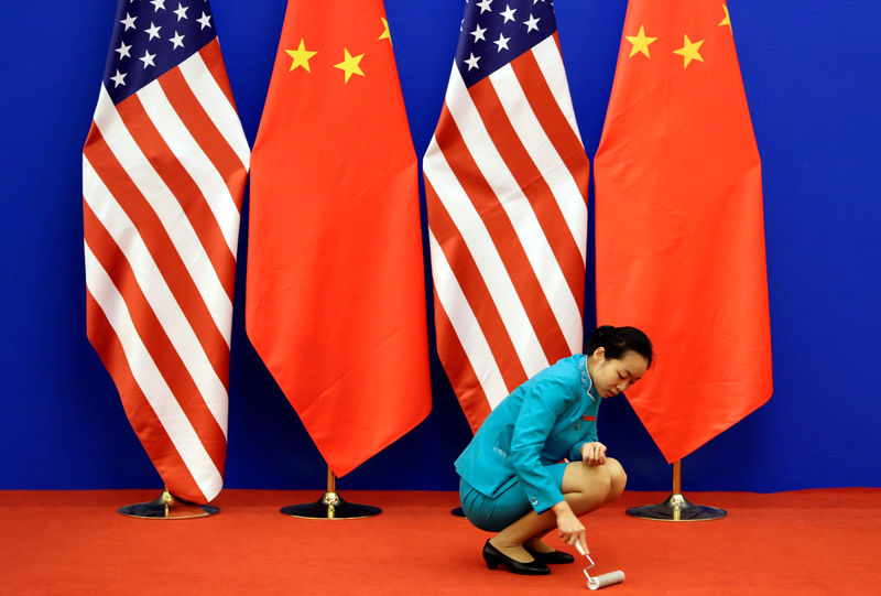 © Reuters. FILE PHOTO: A staff member cleaning the carpet next to the US and Chinese national flags in Beijing