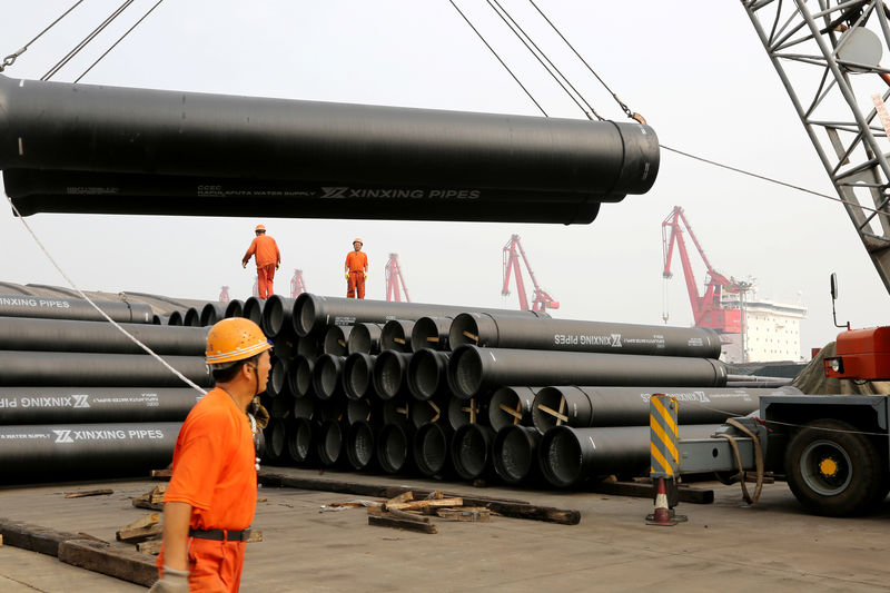 © Reuters. Workers target single-lift steel tubes to export to a port in Lianyungang, Jiangsu