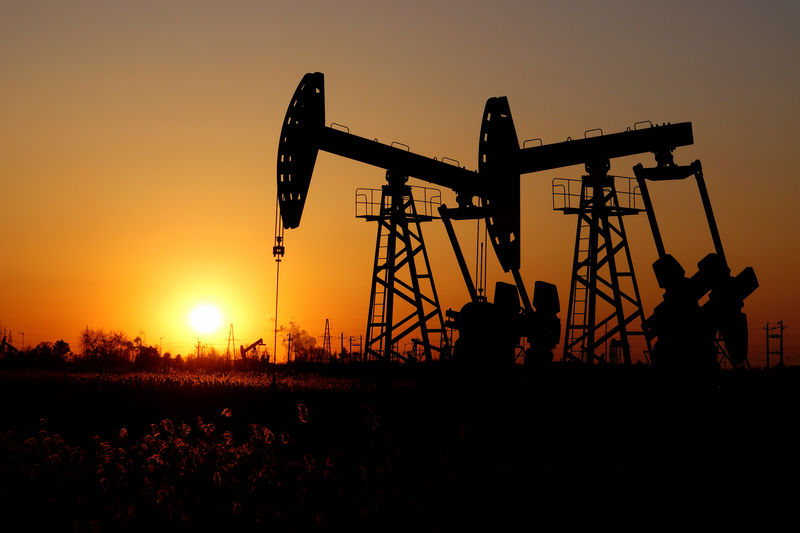 © Reuters. Pumpjacks are seen against the sunset on Daqing oil field in Heilongjiang