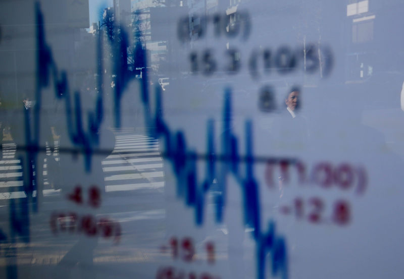 © Reuters. A man reflects on an electronic board displaying a graph analyzing the recent change in the Nikkei stock index in front of a brokerage firm in Tokyo