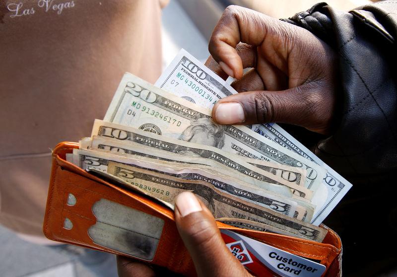 © Reuters. Homem guarda notas de dólar em carteira no Zimbábue