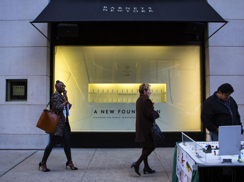 © Reuters. People walk by a Barneys New York retail store in New York
