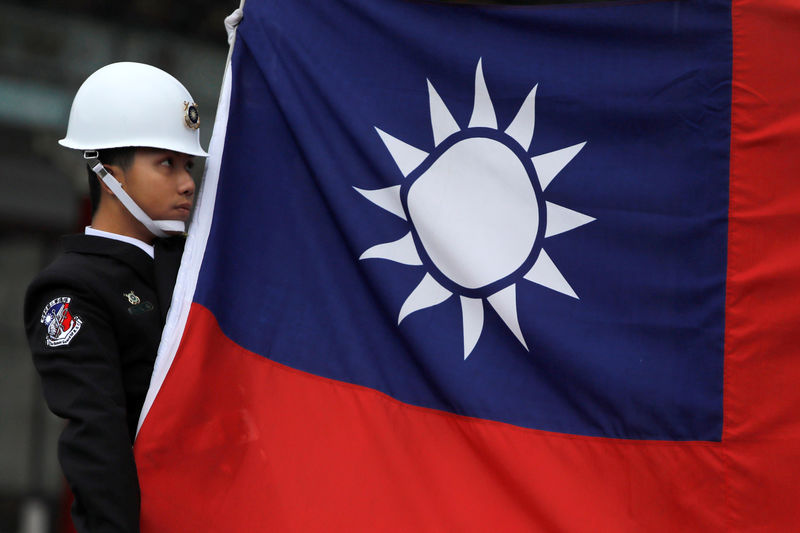 © Reuters. FILE PHOTO: A military honour guard holds a Taiwanese national flag as he attending flag-raising ceremony at Chiang Kai-shek Memorial Hall, in Taipei