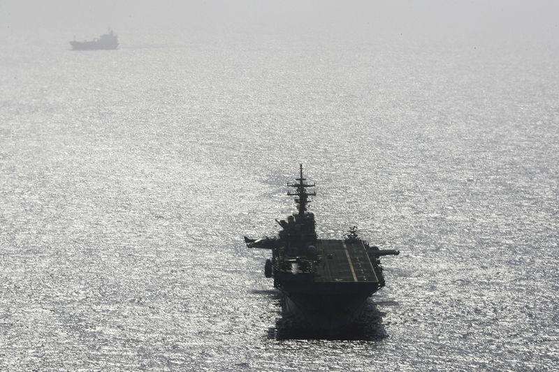 © Reuters. USS Boxer (LHD-4) ship sails near a tanker in the Arabian Sea off Oman