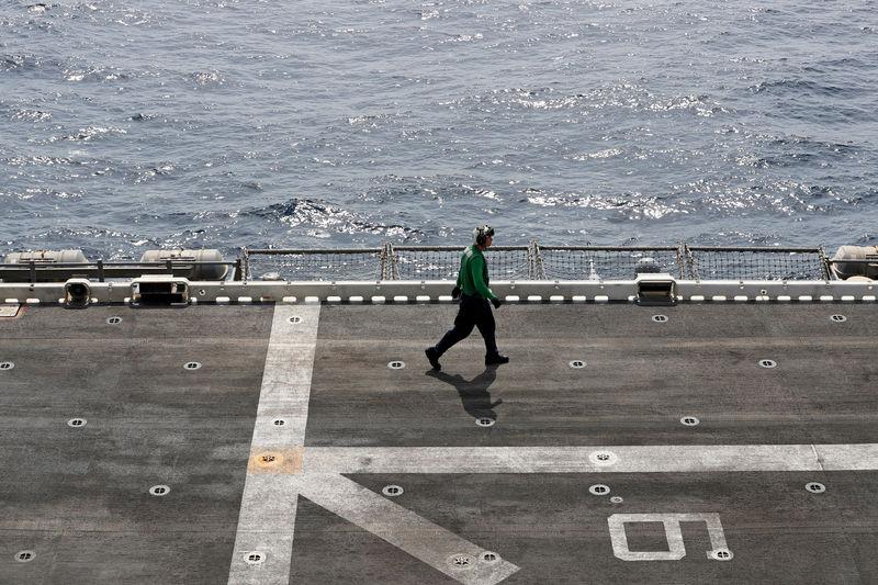 © Reuters. FILE PHOTO: A U.S. sailor walks on the flight deck of USS Boxer (LHD-4) in the Arabian Sea off Oman