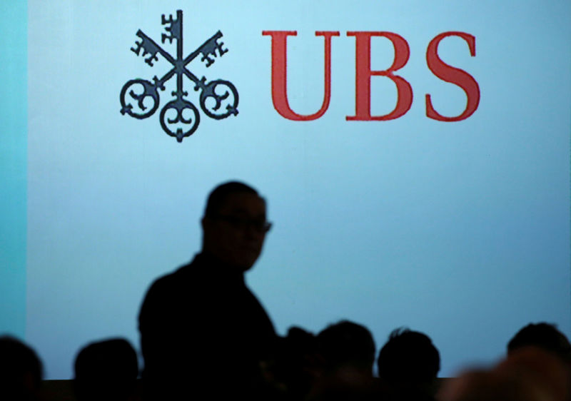 © Reuters. FILE PHOTO: A man walks past a UBS logo projected on a screen in Singapore