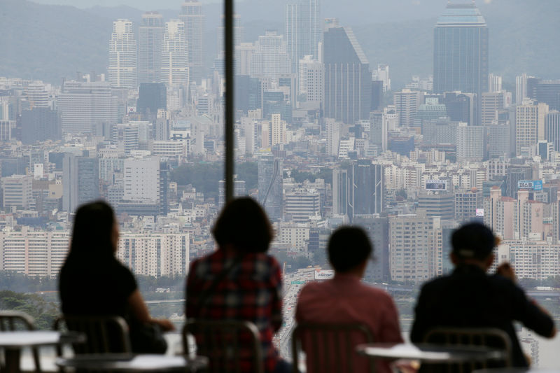 © Reuters. FILE PHOTO: People look at a view of central Seoul from an observatory platform in Seoul