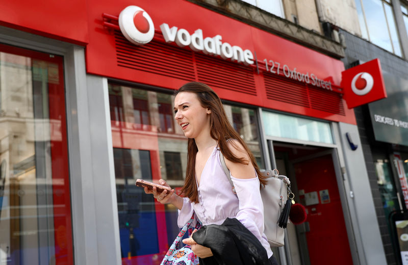 © Reuters. FILE PHOTO: A woman holds a phone as she passes a Vodafone  store in London