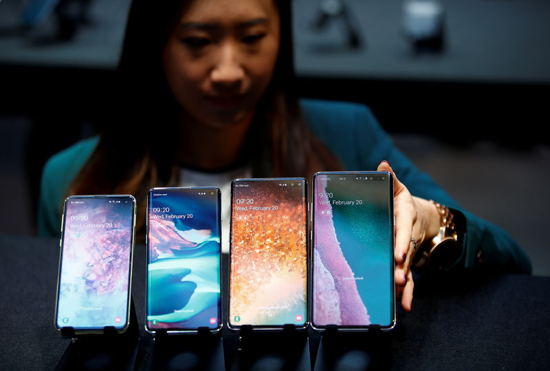 © Reuters. FILE PHOTO: A Samsung employee arranges the new Samsung Galaxy S10e, S10, S10 + and Samsung Galaxy S10 5G smartphones at a press event in London