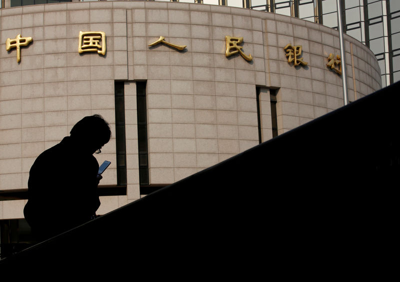 © Reuters. FILE PHOTO: Man sits in front of the headquarters of the People's Bank of China, the central bank, in Beijing