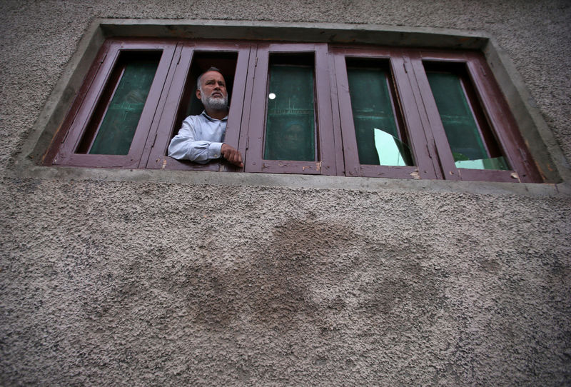 © Reuters. Kashmiri man looks out from a window of his house which was allegedly damaged by Indian security forces after clashes between protesters and the security forces on Friday evening, in Srinagar