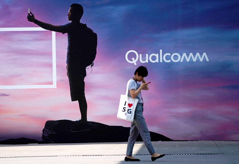 © Reuters. FILE PHOTO: A woman walks past a sign advertising Qualcomm at Mobile World Congress (MWC) in Shanghai