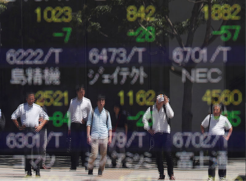 © Reuters. Passersby are reflected on a stock quotation board outside a brokerage in Tokyo