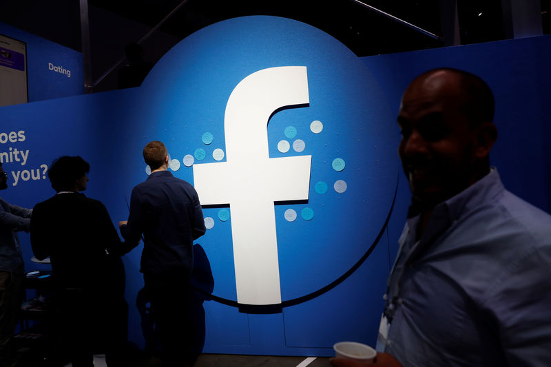 © Reuters. FILE PHOTO: Attendees walk past a Facebook logo during Facebook Inc's F8 developers conference in San Jose