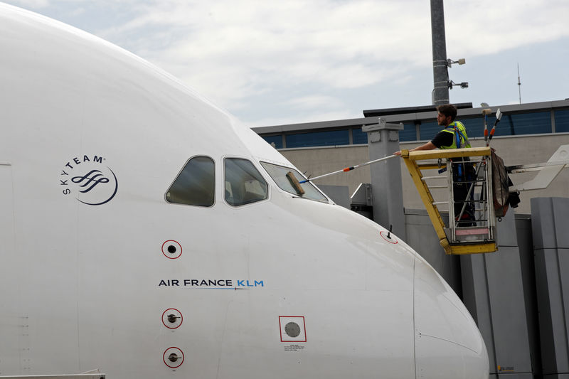 © Reuters. FILE PHOTO: A worker cleans the windshield of an Air France-KLM plane at the Paris Charles de Gaulle Airport in Roissy