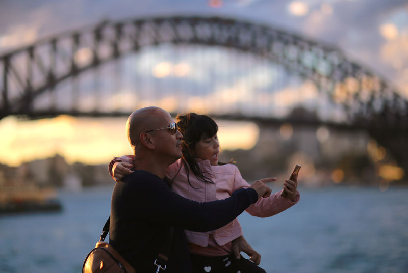 © Reuters. FILE PHOTO: Tourists look at a phone as they stand in front of the Sydney Harbour Bridge at sunset in Australia