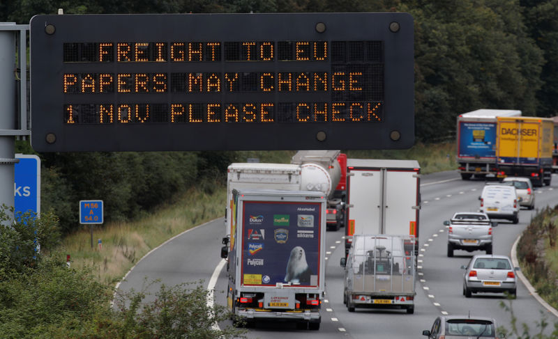 © Reuters. Vehicles pass beneath a sign warning of possible changes to freight procedures following Brexit on the M56 motorway near Chester, Britain