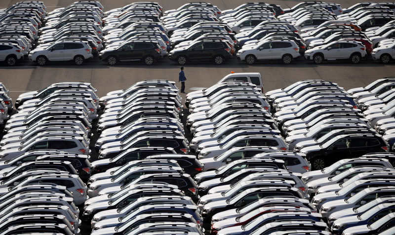 © Reuters. FILE PHOTO: A worker is seen among newly manufactured cars awaiting export at port in Yokohama