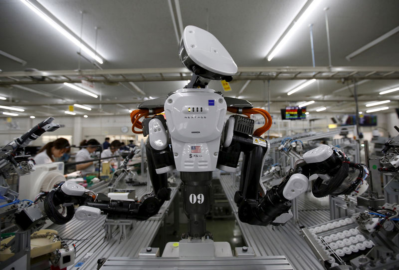 © Reuters. FILE PHOTO: A humanoid robot works side by side with employees in the assembly line at a factory of Glory Ltd., a manufacturer of automatic change dispensers, in Kazo, north of Tokyo