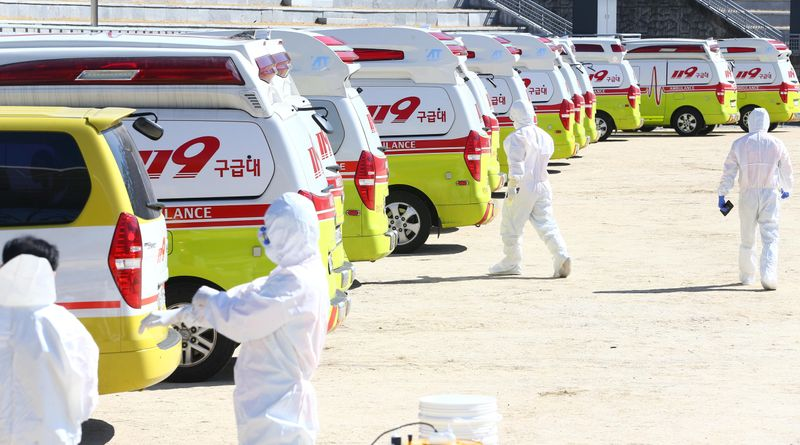 © Reuters. Medical workers get ready as ambulances are parked to transport a confirmed coronavirus patient in Daegu