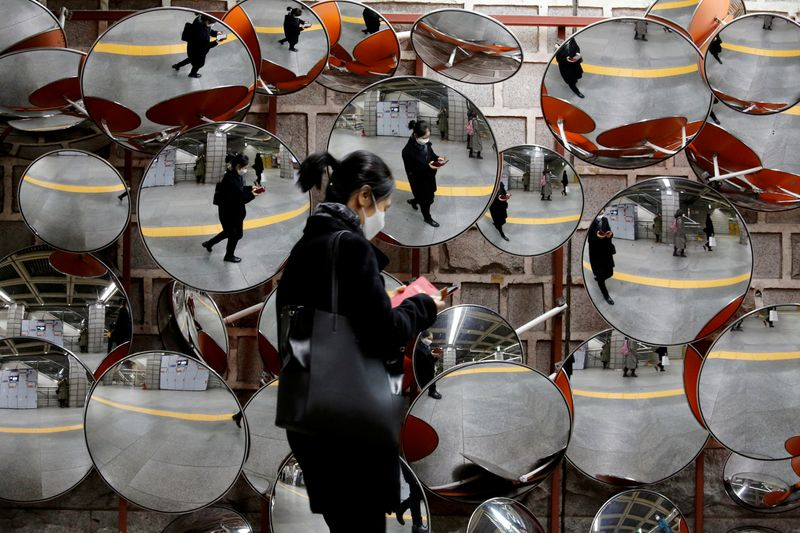 © Reuters. FILE PHOTO: Woman wearing a mask to prevent the coronavirus is reflected on the mirrors, in Seoul