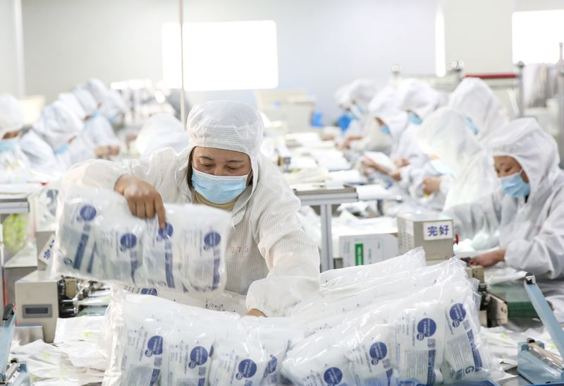 © Reuters. Employees work on a medical supply production line at a factory in Huaian