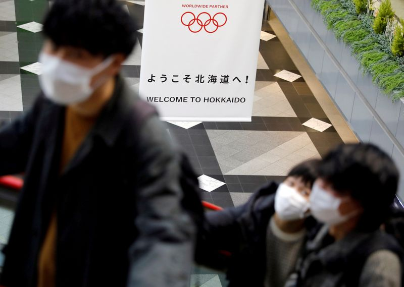 © Reuters. FILE PHOTO: Passengers wearing protective face masks, following an outbreak of the coronavirus, are seen near a campaign banner for Tokyo 2020 Olympic Games at New Chitose Airport in Chitose, Hokkaido
