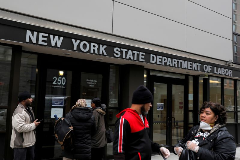 © Reuters. FILE PHOTO:  People gather at the entrance for the New York State Department of Labor offices, which closed to the public due to the coronavirus disease (COVID-19) outbreak in the Brooklyn borough of New York City