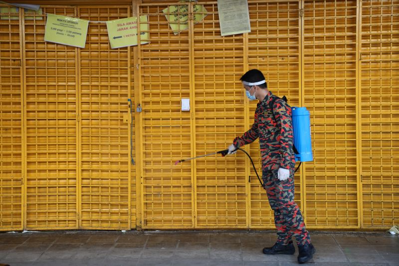 © Reuters. FILE PHOTO:  A firefighter disinfects a closed shop during the movement control order due to the outbreak of the coronavirus disease (COVID-19), in Kuala Lumpur