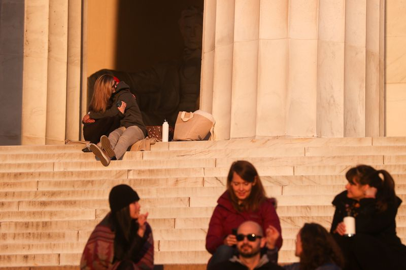 © Reuters. A couple embrace as a few people take to the steps at the Lincoln Memorial during the coronavirus disease (COVID-19) outbreak, where normally thousands of Christians would gather for worship at Easter sunrise, in Washington