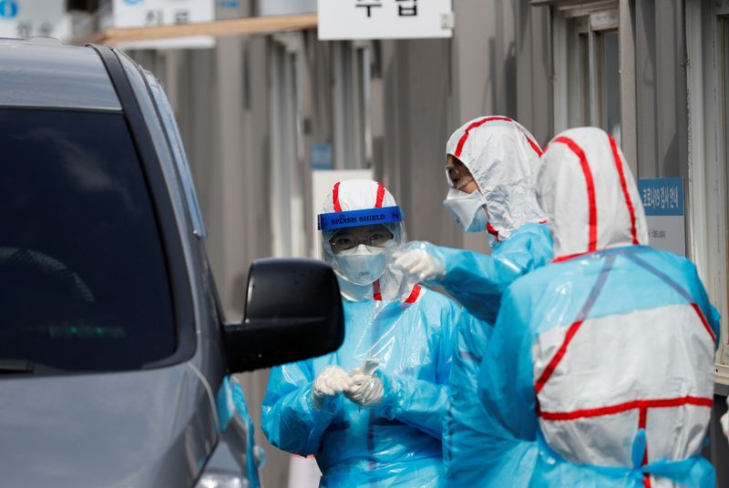 © Reuters. FILE PHOTO: Medical staff in protective gear prepare to take samples from visitors in their cars at a 'drive-thru' testing center for the novel coronavirus disease of COVID-19 in Yeungnam University Medical Center in Daegu