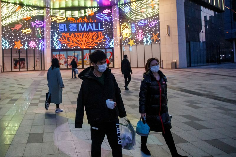 © Reuters. FILE PHOTO: People wear face masks outside a shopping mall in Beijing as the country is hit by an outbreak of the novel coronavirus