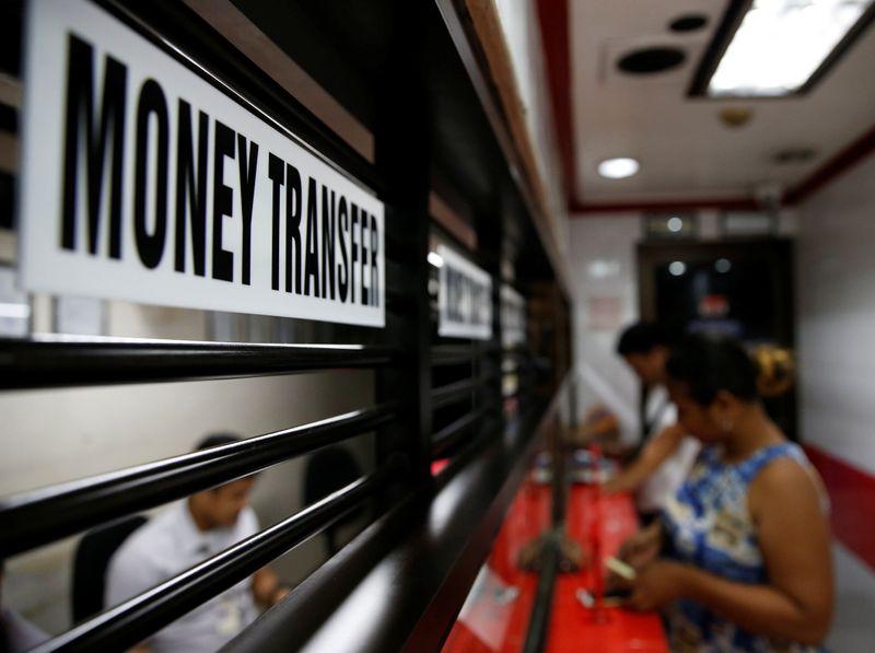 © Reuters. Klienci otrzymują pieniądze z rodziny pracuje za granicą na pieniądze, centrum tłumaczeń w Makati