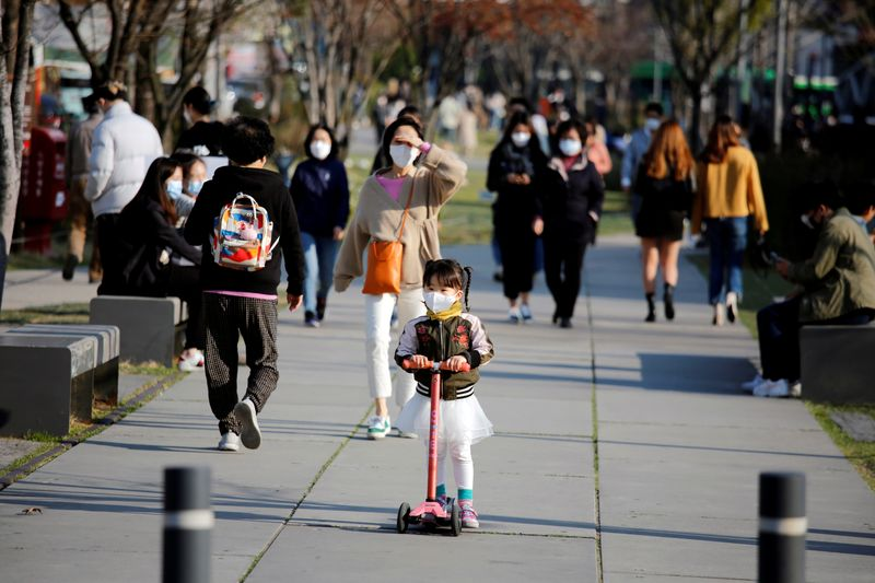 © Reuters. FILE PHOTO: A girl wearing a protective face mask rides a toy scooter at a park in Seoul,