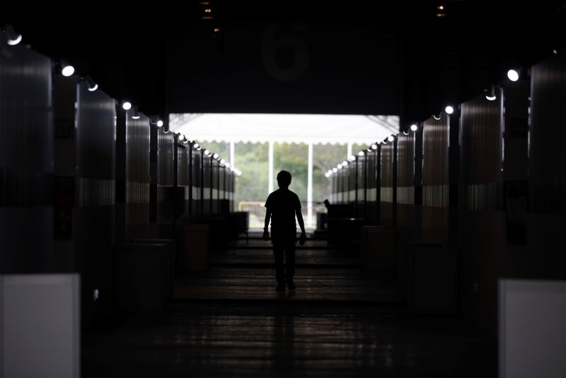 © Reuters. A man walks past partitioned rooms at Changi Exhibition Centre which has been repurposed into a community isolation facility, in Singapore