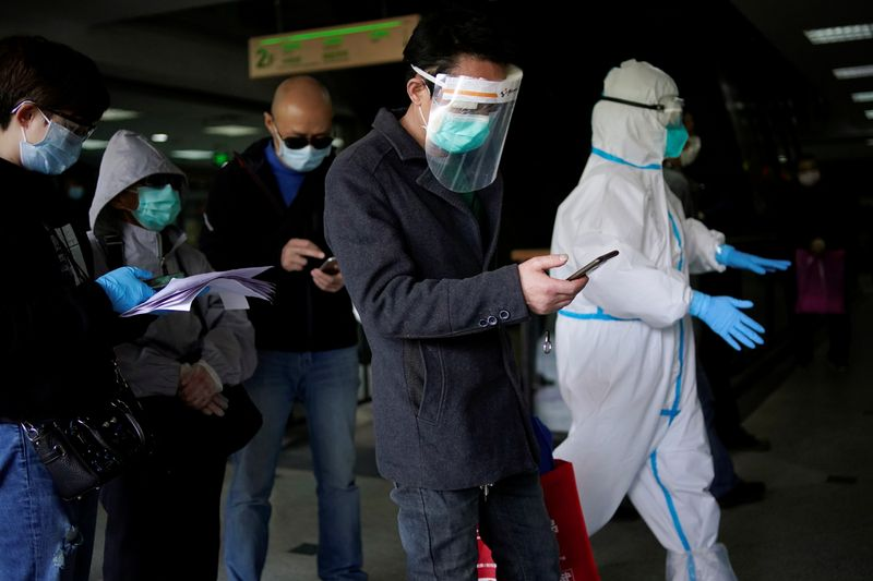 © Reuters. FILE PHOTO:  Trader He Ximing, 52, a recovered COVID-19 patient who tested positive for the virus' antibodies after a number of negative tests, walks past a blocked fresh food market after the lockdown was lifted in Wuhan