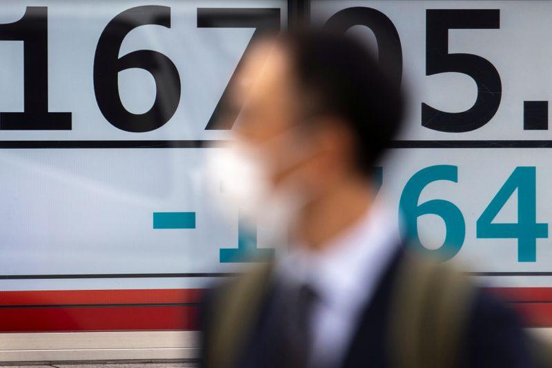 © Reuters.  Một người đàn ông đeo mặt nạ bảo vệ bước qua màn hình hiển thị chỉ số Nikkei bên ngoài một công ty môi giới ở Tokyo