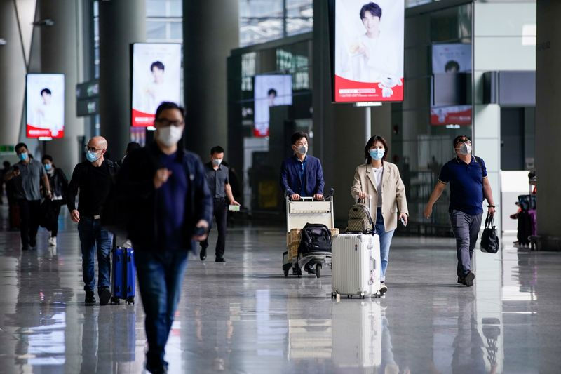 © Reuters. FILE PHOTO: People wearing face masks are seen at Hongqiao International Airport in Shanghai