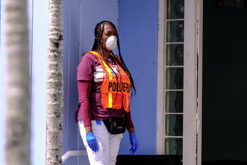 © Reuters. FILE PHOTO: A poll deputy wears gloves and a mask as a preventive measure against the outbreak of coronavirus disease (COVID-19), during the Democratic presidential primary election in Miami