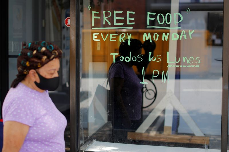 © Reuters. A pedestrian passes a notice for a food pantry in Chelsea