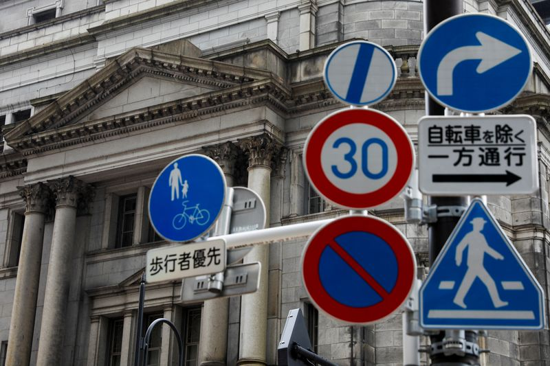 © Reuters. FILE PHOTO: Traffic signs are seen in front of the headquarters of the Bank of Japan