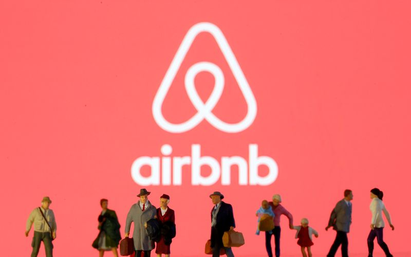 © Reuters. Small toy figures are seen in front of diplayed Airbnb logo